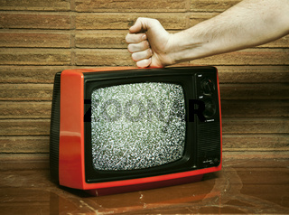 A man's fist smashing a static filled television