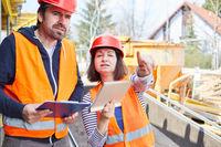 Arbeiter und Architektin zusammen bei der Bauplanung