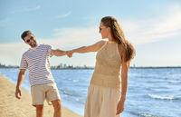 happy couple walking along summer beach