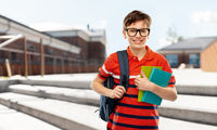smiling student boy with backpack and books