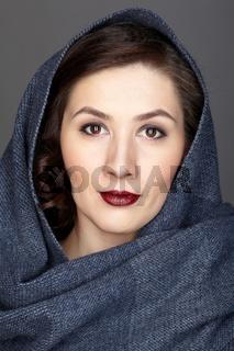 Beauty portrait of brunette woman dressed in dark blue scarf.