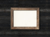 Old rustic wooden picture frame hanging on a black wall. Horizontal picture