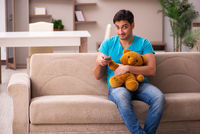 Young man sitting with bear toy at home