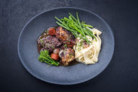 Modern style traditional French coq au vin with vegetable marinated in Burgundy sauce as top view in a design plate