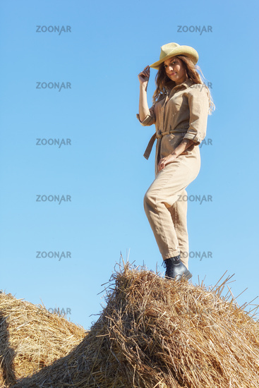 Young blonde woman in a beige jumpsuit stands on on the rolls of hay.
