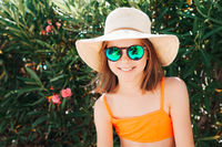 Little smiling playful girl in a straw hat and sunglasses - looking directly at the camera - against the background of a bush with flowers - carefree concept
