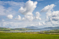 View from Kerry Cliffs on Portmagee village and farms with fiord and mountain range in background