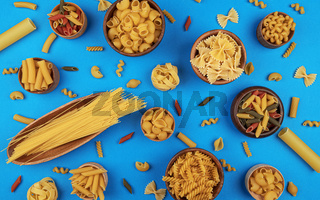 Different pasta types on blue background, top view, flat lay
