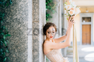 Bride lowered her eyes, leaning against a pillar with raised hands with a bouquet of flowers. Lake Como