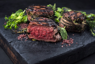 Traditional barbecue dry aged angus medaillon beef filet steak natural with herbs and chili served as close-up on a charred wooden board
