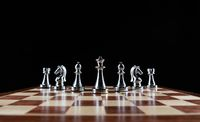 Silvery chess figures standing on chessboard