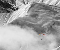 Paragliding at snow mountains in haze. Black and white toned image. Selective color effect.
