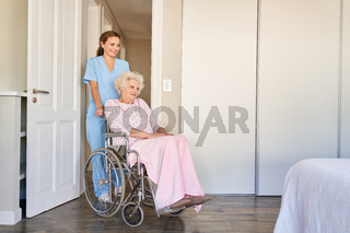 Altenpflegerin oder Pflegehilfe schiebt Seniorin im Rollstuhl