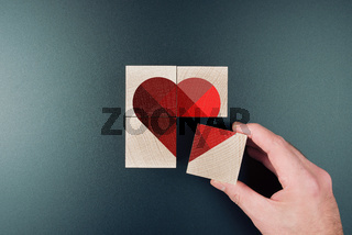 above view of person piecing together heart shape on wooden blocks