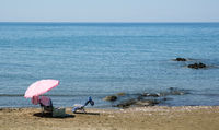 Beach umbrella and relaxing chair on a sandy coast in summer. Summertime holidays
