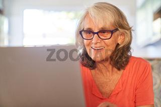 Lächelnde Seniorin beim Videochat am Laptop Computer