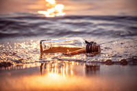 Message in the bottle against the Sun setting down