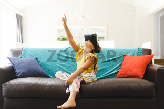 Caucasian girl sitting on couch and using vr headset in living room