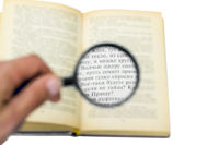 open book under a magnifying glass isolated on whi