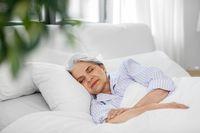senior woman sleeping in bed at home bedroom