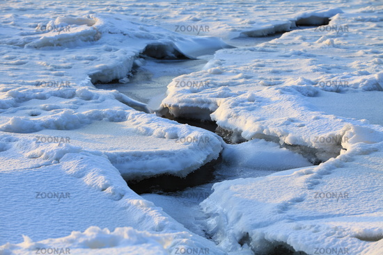 deep winding crack in the ice of a frozen river