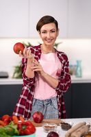Apple in hand happy woman select fruits cooking at new kitchen looking at camera. Housewife cooking apple pie standing at the kitchen wearing plaid shirt with a short hair