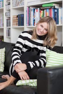 Junge Frau sitzt gemütlich auf dem Sofa