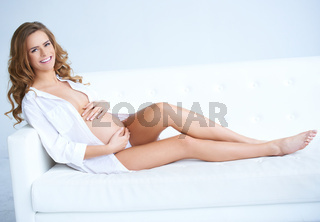 Happy pregnant young woman on sofa