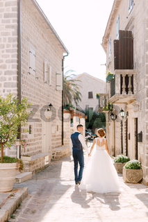 The bride and groom walk along a cozy narrow street of the old town of Perast holding hands, back view