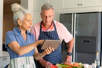 Happy caucasian senior couple standing in kitchen, using tablet and preparing meal together