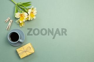 Yellow gift box, flower bouquet, cup of coffee on green background. flat lay, top view, copy space
