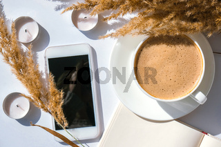 Pampas grass and white cup with coffee. Mobile phone with black screen. Checking social media Drinking Cappuccino in the breakfast morning at home. Flat lay. Wallpaper. Aesthetics