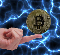 Bitcoin cryptocurrency coin balancing on a finger with blue electricity background