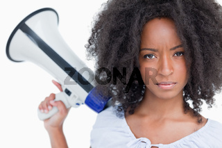 Young serious woman holding a megaphone behind her