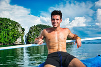 Handsome shirtless man relaxing on a boat
