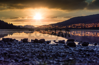 Sunset at Rotevatnet in Volda, Norway with citylights in background and stones in forefront