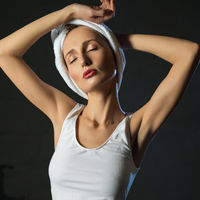 Slim girl in white top and towel on her head view