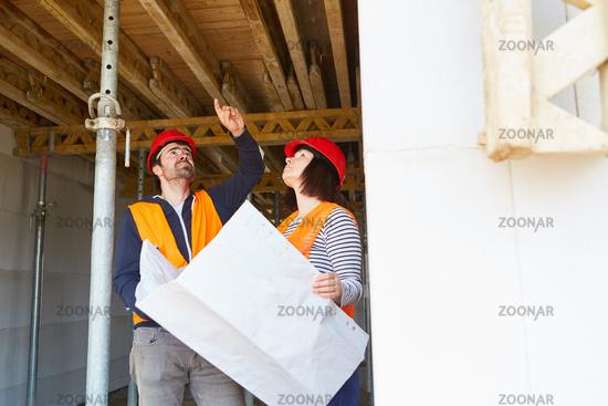 Architektin und Handwerker kontrollieren Holzdecke