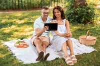 happy couple with tablet pc at picnic in park