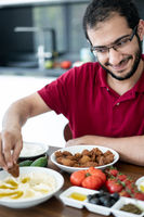 Middle Eastern young man sitting and eating traditional food