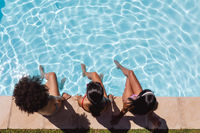 Diverse group of female friends sitting at the poolside