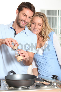 Couple using peppper grinder