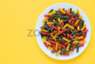Red green and yellow dry raw fusilli pasta on a plate with yellow background and copy space.