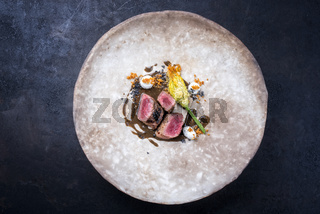 Modern style traditional wild hare back filet braised with fiori di zucchini fritti in game jus served as top view on a rustic design plate with copy space