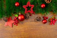 Composition of christmas decorations with fir tree, baubles and copy space on wooden background