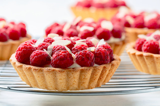 Mini tartlets with custard and raspberries.