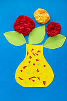 Children of paper applique flowers on a blue backg