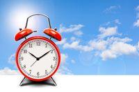 Red alarm clock on blue sky background