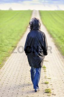 Frau auf einem Feldweg