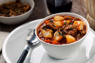 Hot stew with potatoes on a plate. High quality photo.